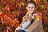 Portrait of relaxed woman with autumn leafs in front of foliage