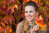 Portrait of pensive woman with leafs in front of autumn foliage