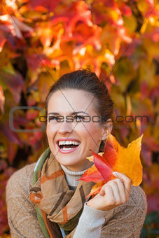 Portrait of cheerful woman with autumn leafs in front of foliage