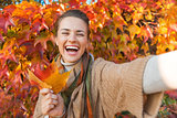 Portrait of cheerful young woman with autumn leafs making selfie