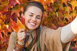 Portrait of happy relaxed woman with autumn leafs making selfie