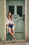 Pensive hippy-looking woman standing outdoors against door