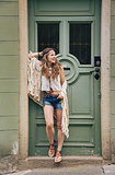 Happy hippy-looking woman standing outdoors against wooden door