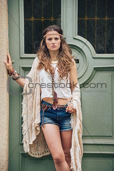 Portrait of hippy-looking woman standing outdoors against door
