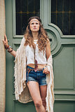 Portrait of young boho chic standing outdoors against door