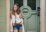 Portrait of trendy hipster woman standing outdoors against door