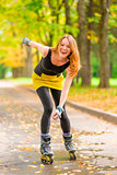 beautiful cheerful girl roller skate active in the autumn park
