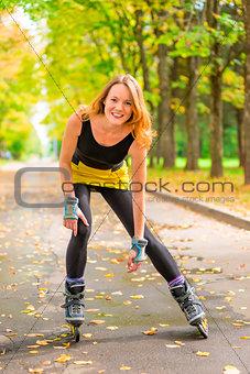 athlete posing on skates in the autumn deserted park