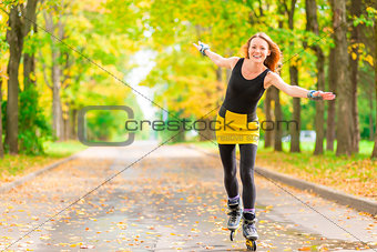 slender red-haired girl on roller skates rolling