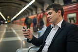 Businessman with smartphone in subway