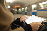 Tablet in female hands showing subway map in underground