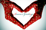 hands forming a heart and the sentence seasons greetings