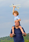 Father carrying son and his plane