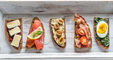 Bruschetta with different toppings on the wooden tray