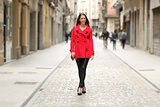 Fashion woman in red walking on a city street