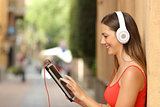 Girl browsing a tablet and listening with headphones