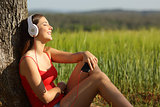 Girl listening to the music relaxed in a green field