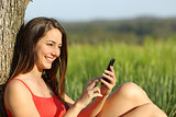 Girl texting in a smart phone relaxed in the country