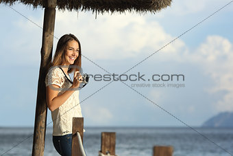 Tourist traveler girl enjoying holidays looking a seascape on the beach