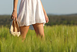 Relaxed woman legs walking in a field in summer