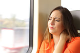 Stressed woman with neck ache in a train wagon