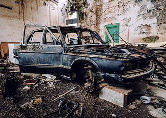 Old wrecked car inside of ruinous building