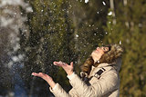 Happy girl throwing snow in the air on winter holdays