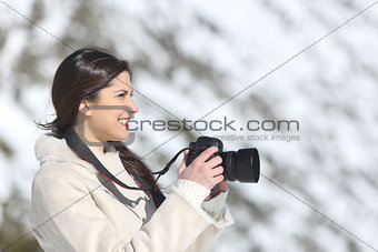 Tourist woman photographing on winter holidays