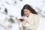 Woman playing games in a smart phone on winter holidays