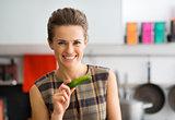 Smiling woman holding fresh cucumber