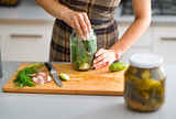 Closeup of woman's hands preparing cucumbers for dill pickles