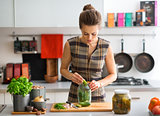 Woman in kitchen preparing dill pickles