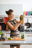 Smiling and elegant woman in kitchen holding up jar of pickles