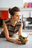 Elegant woman leaning on kitchen counter holding jar of pickles