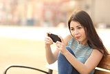 Funny teenager playing games on a smart phone