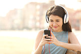 Girl listening music with headphones from a smart phone