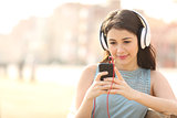 Girl searching songs and listening music with headphones