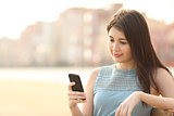 Pretty girl using a mobile phone in an urban park