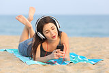 Teen girl listening music and singing on the beach