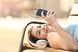 Teen girl listening music from a phone lying in a bench