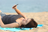Teen girl lying and using a smart phone