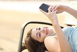 Teen girl using a smart phone lying in a bench