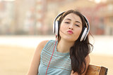 Teenager girl with headphones kissing at camera