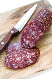 Sliced dry sausage and knife.