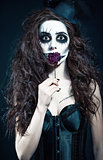 Young woman in the image of sad gothic freak clown holds withered flower