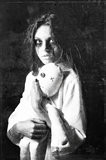 Horror style shot: mysterious ghost girl with moppet doll in hands. Grunge texture effect