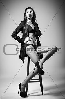 Beautiful sexy young woman in black underwear and jacket sitting on chair. Black and white