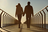 Back silhouette of a couple walking holding hands