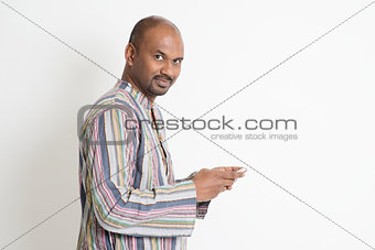 Mature casual Indian man playing smartphone games