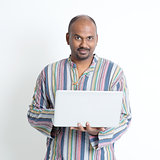 Mature casual Indian man using laptop